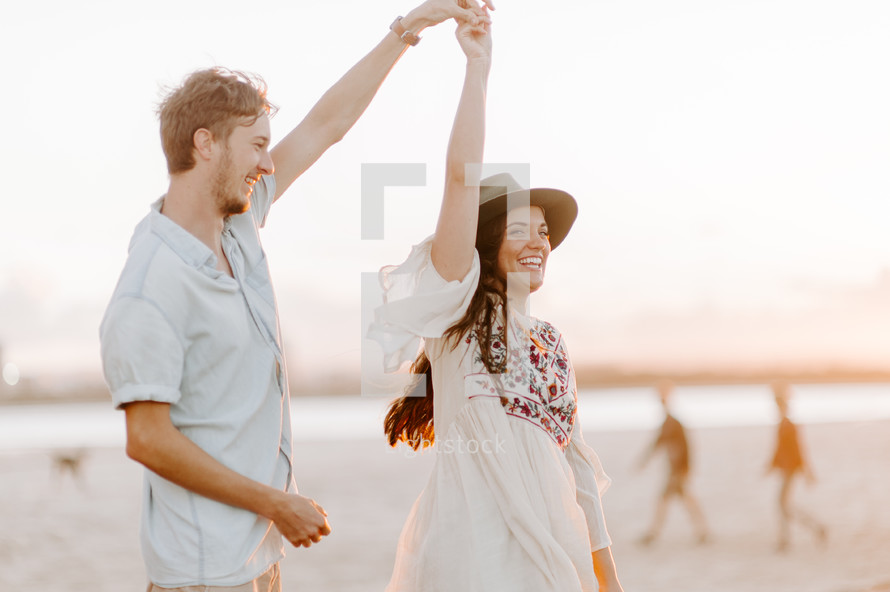 a cheerful couple dancing on a beach