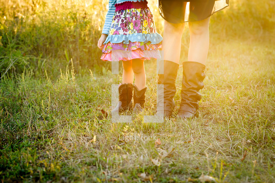feet of a mother and daughter wearing cowboy boots