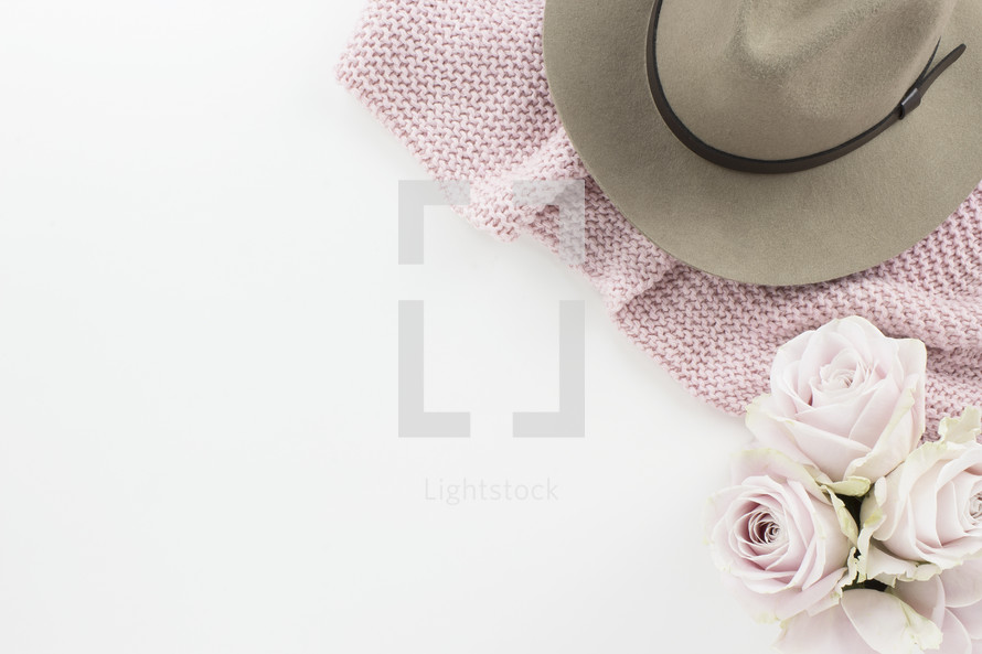 hat on a pink scarf and flowers