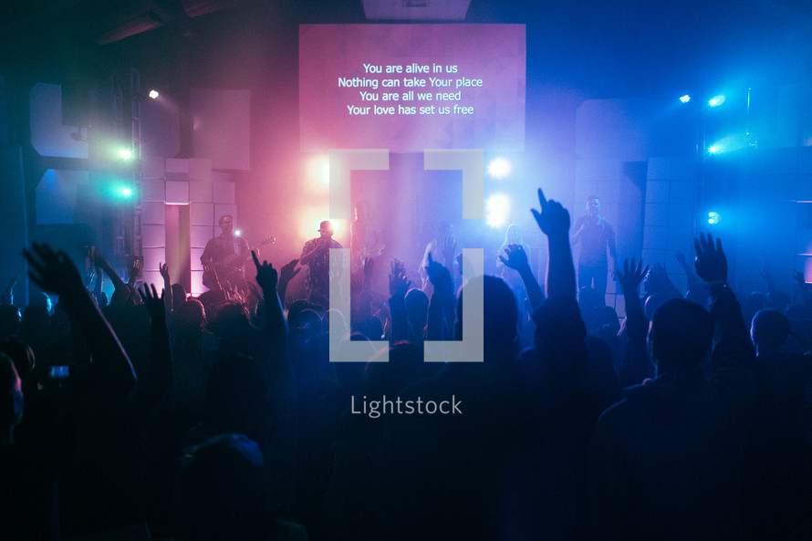 projection screen and raised hands at a contemporary worship service