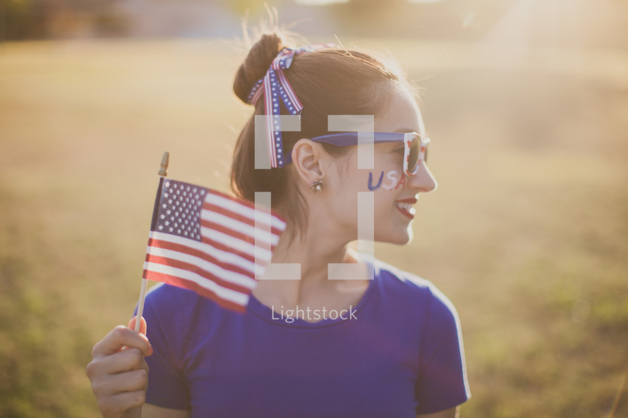 woman holding an American flag and USA face paint