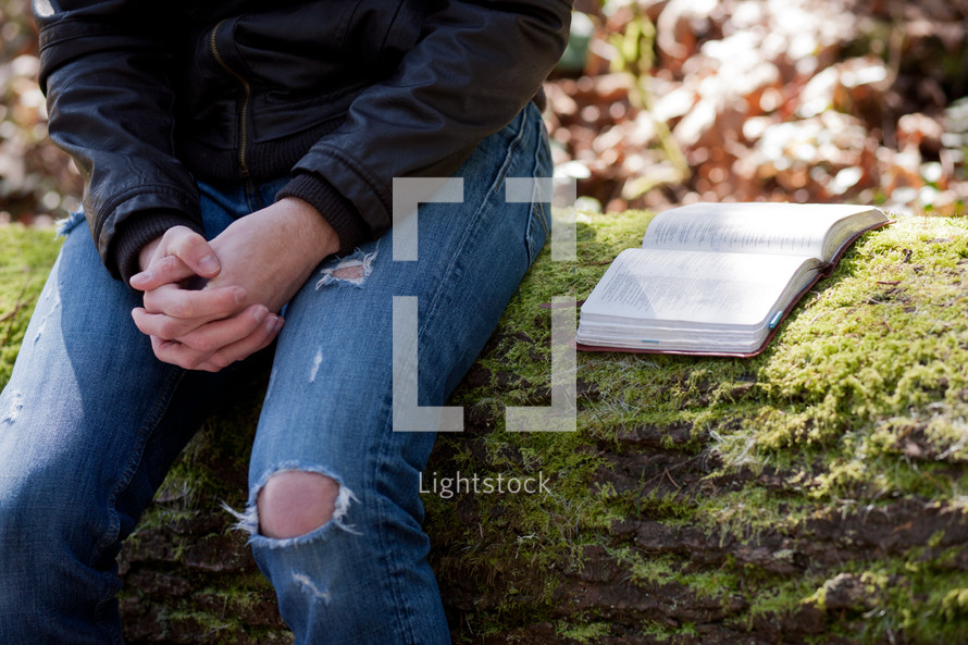 Man in ragged jeans sitting on a mossy log, hands folded, with open Bible.