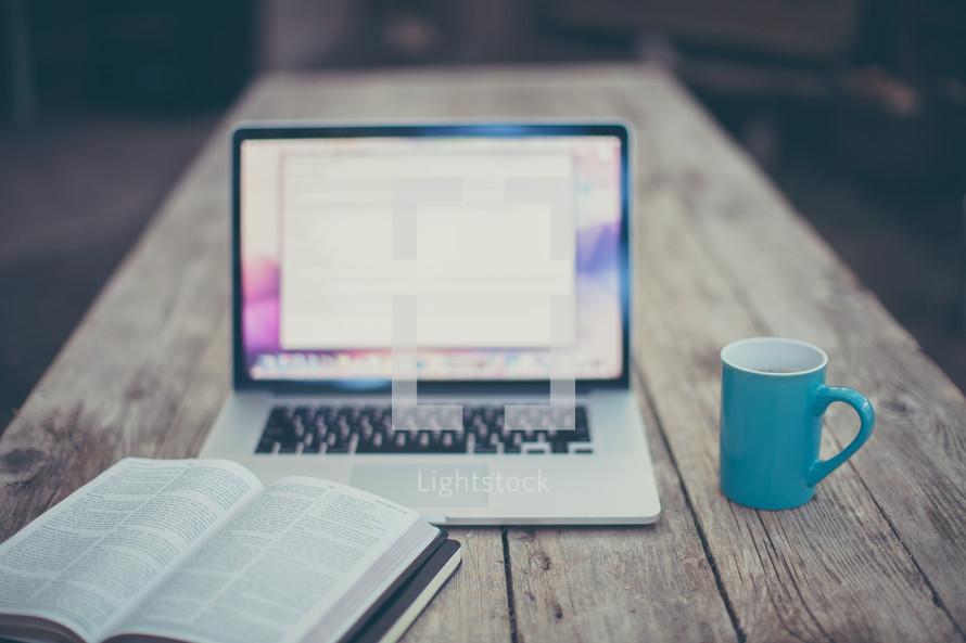 open Bible, journal, computer screen, and coffee mug