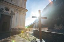 cross in sunlight in front of a church