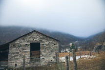 stone barn and fence on a mountainside
