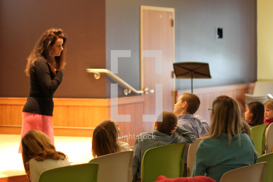 Teacher lecturing an auditorium of students.