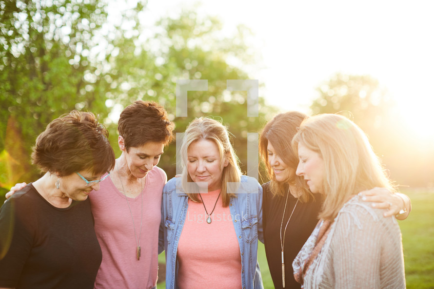 women standing in a backyard praying together
