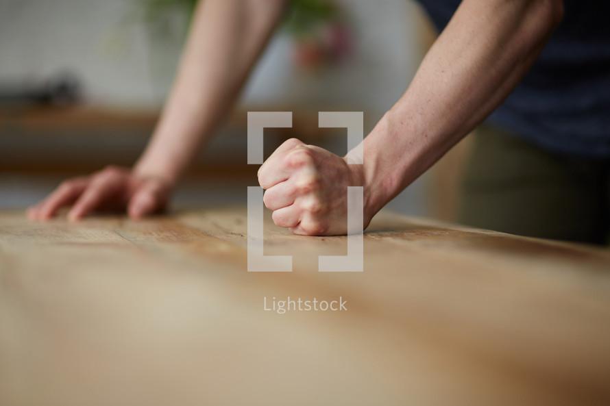 a man pounds his fist on a desk.
