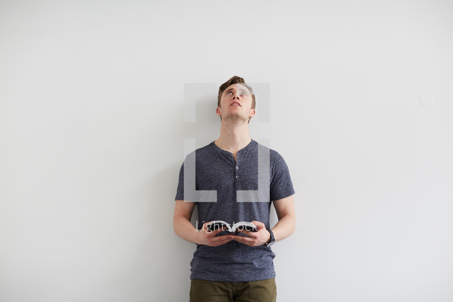 a man standing holding a Bible and looking up to God