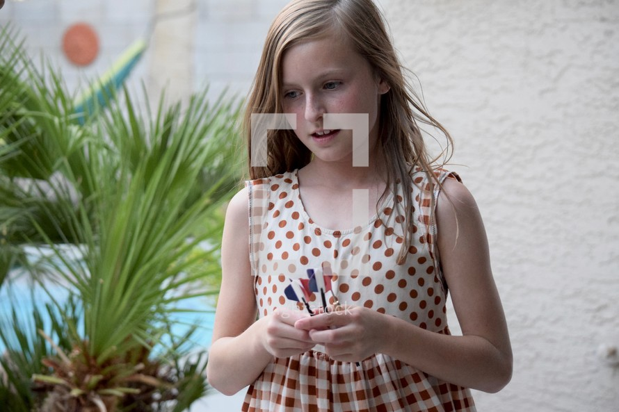 a little girl holding darts,