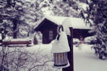 snow on a cabin and lantern