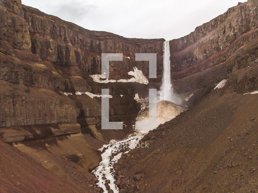waterfall flowing over brown cliffs