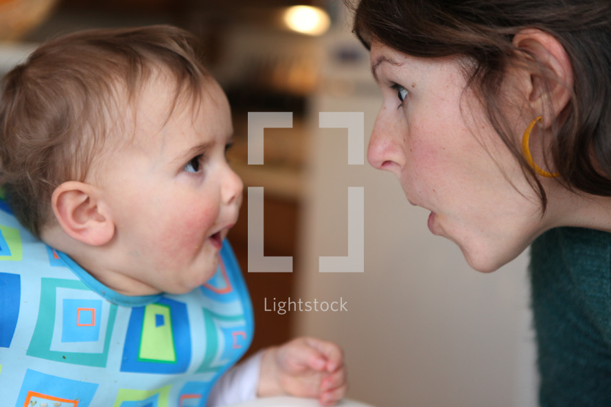 mother and infant son making silly faces