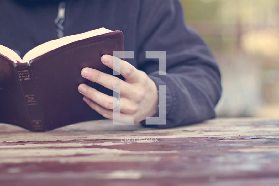 man reading a Bible at a picnic table