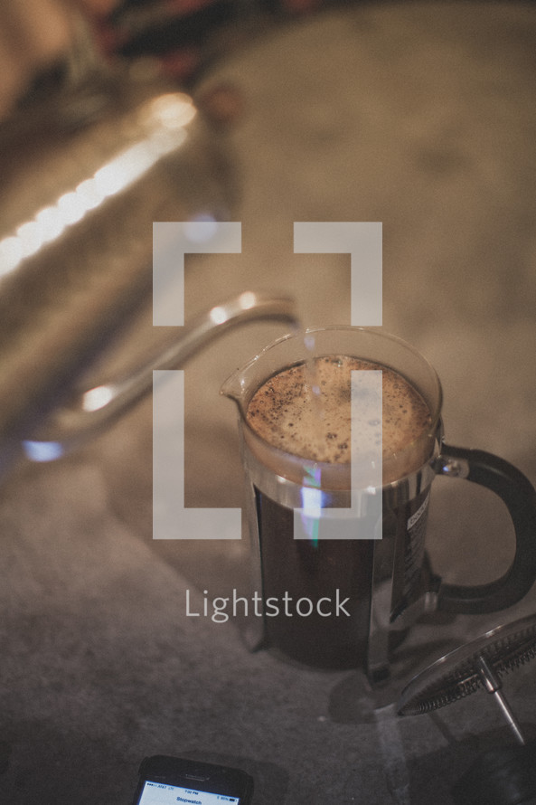 Pouring hot water from a kettle into a french press