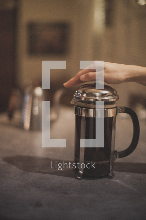 A hand pressing down on a French Press