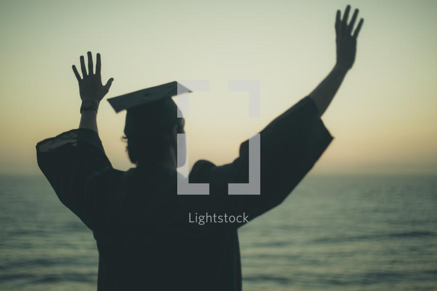 silhouette of a graduate on a beach
