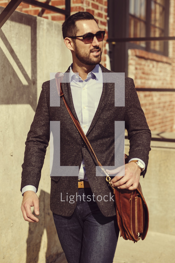 a man in a blazer carrying a satchel, walking to work
