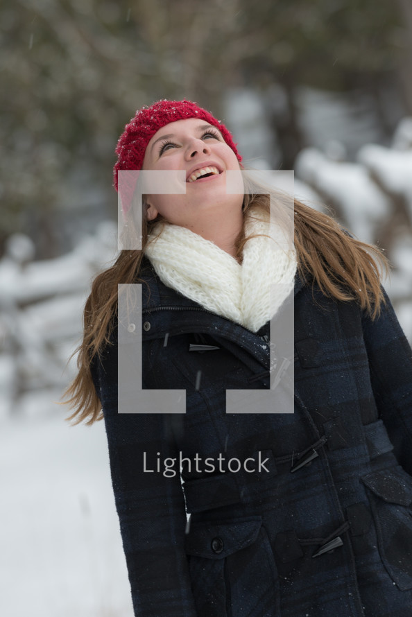 a woman looking up at the falling snow