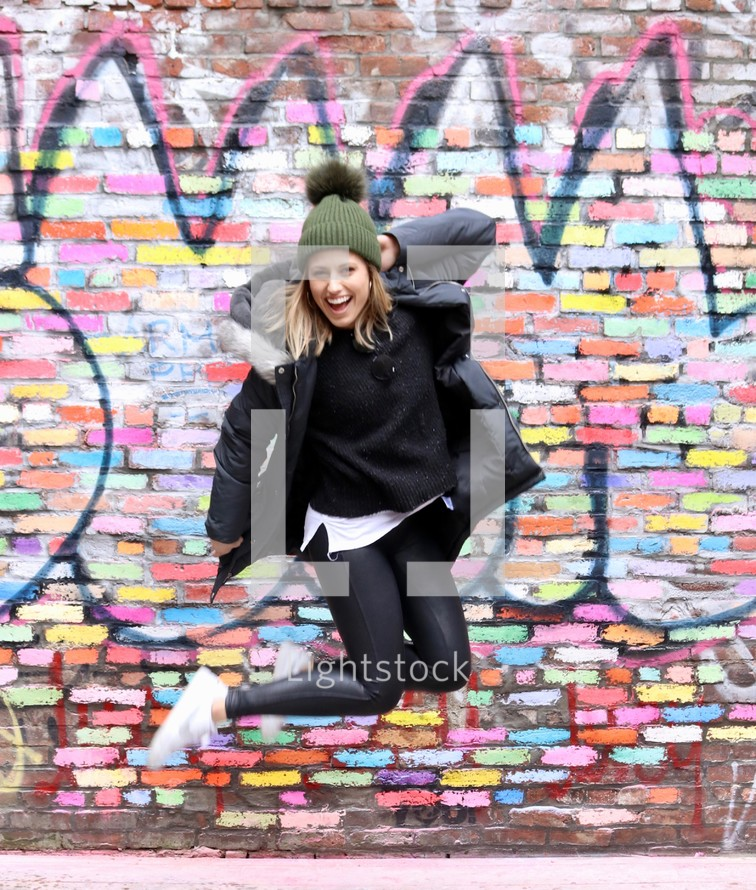 young woman jumping up in front of a graffiti covered wall