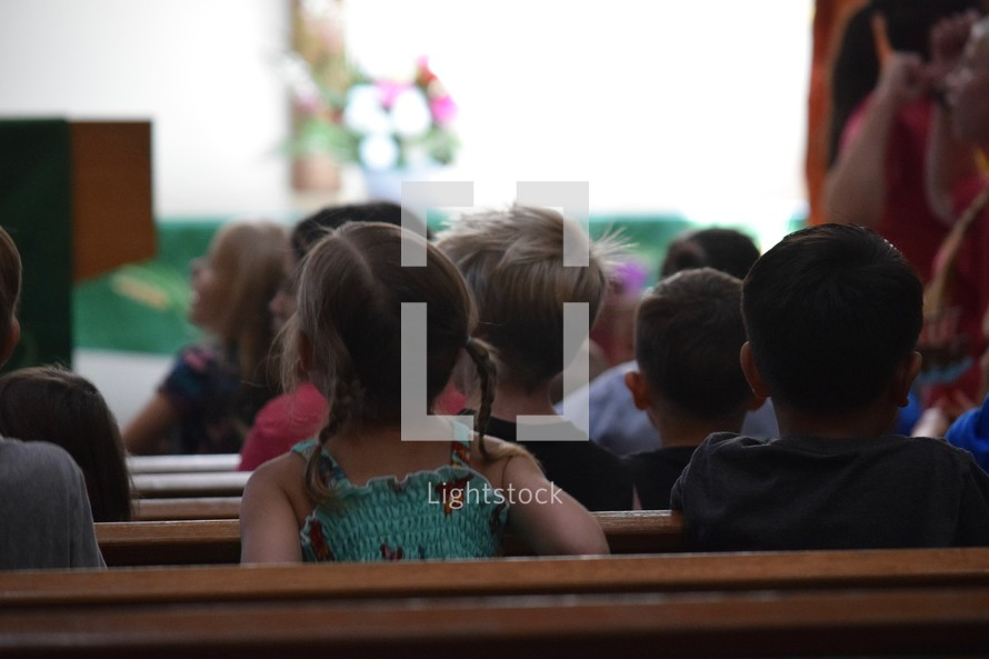 group of young children sitting in church pews listening