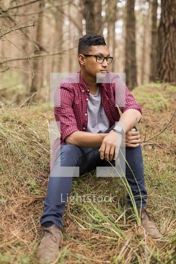 a young man sitting on a hill in the grass