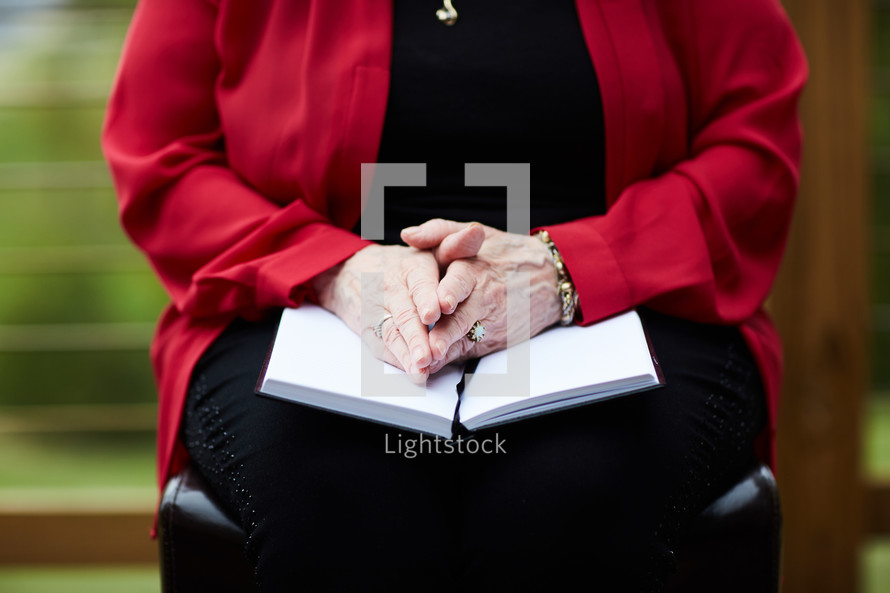woman with her hands on a Bible in her lap