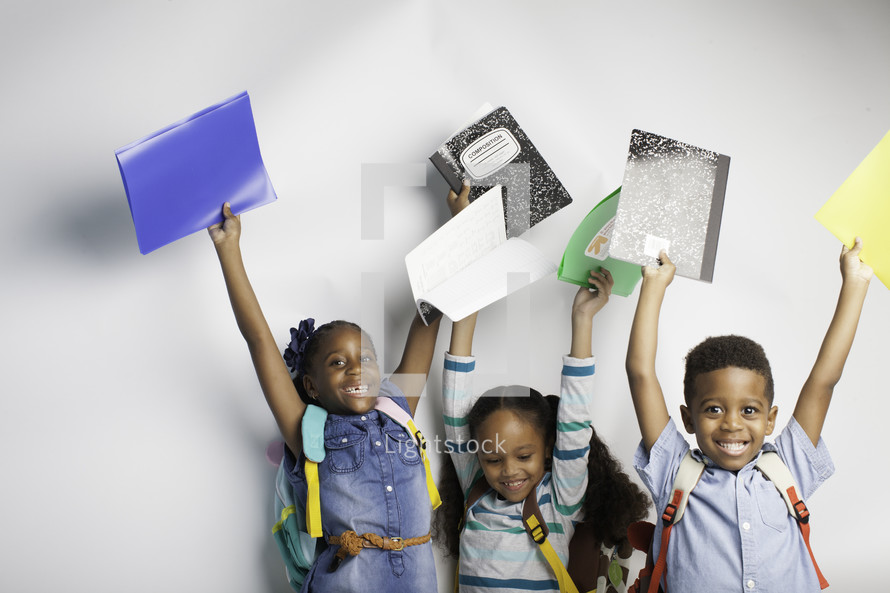 kids holding up school supplies for the first day of school