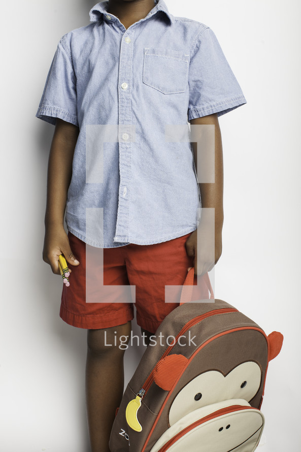 a child holding his book bag