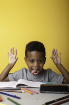 a boy child sticking out his tongue at a table