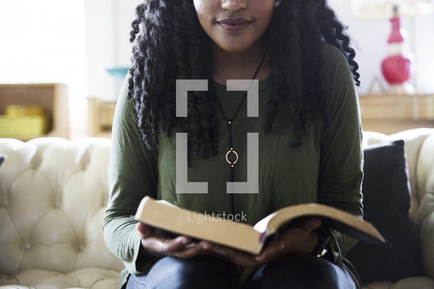 an African American woman reading a Bible on a couch