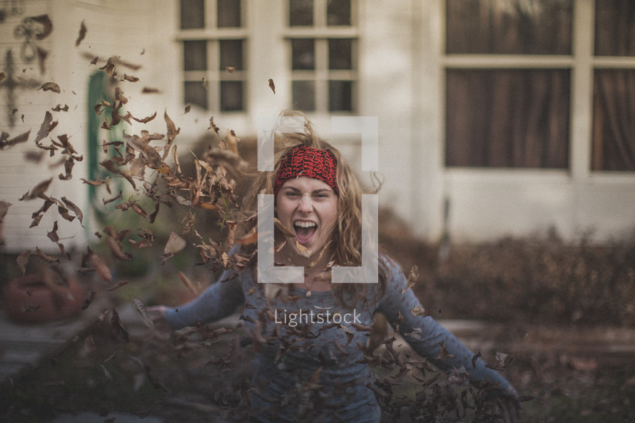 A blonde girl throwing fall leaves in the air