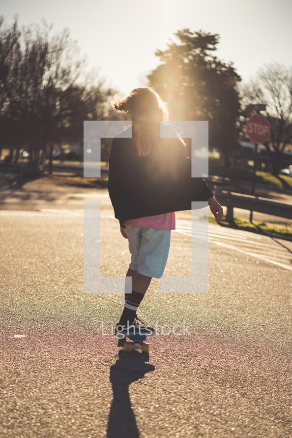 a teen girl skateboarding at sunset