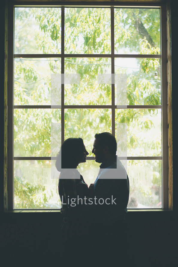 a couple standing in front of a window