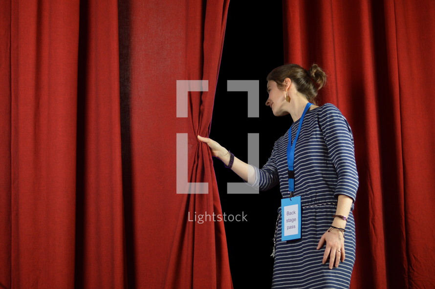 a woman checking behind the curtains on stage, back stage pass