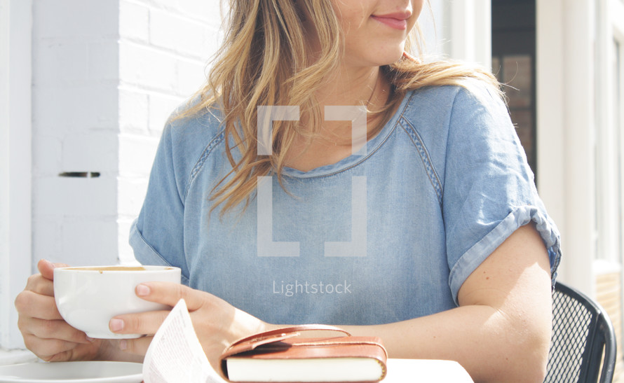 a woman sitting at an outdoor table with a coffee cup, Bible, and journal