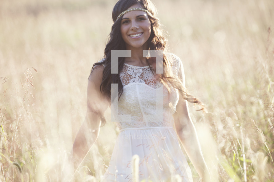 Smiling woman in a field of tall grass.