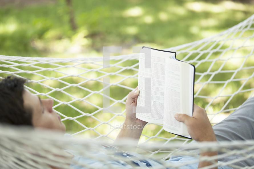 man reading a Bible in a hammock.