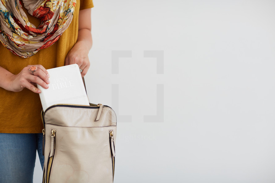 a woman putting a Bible in her purse