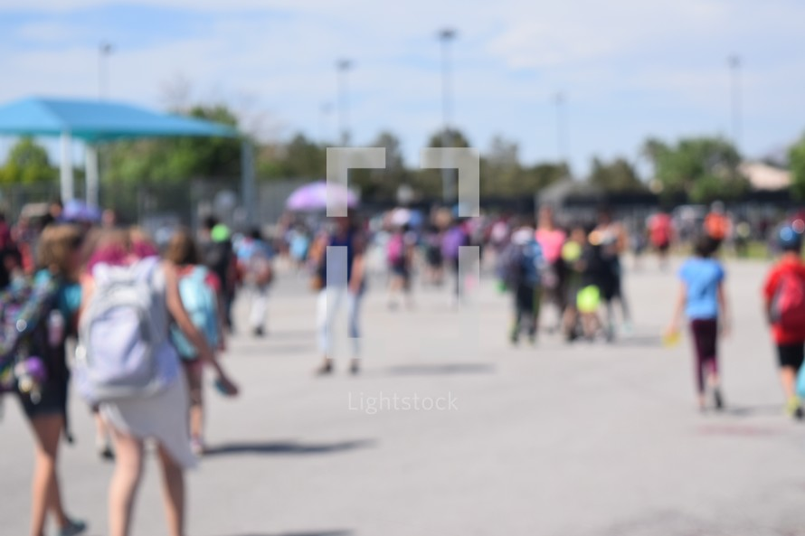 blurry students in a school yard