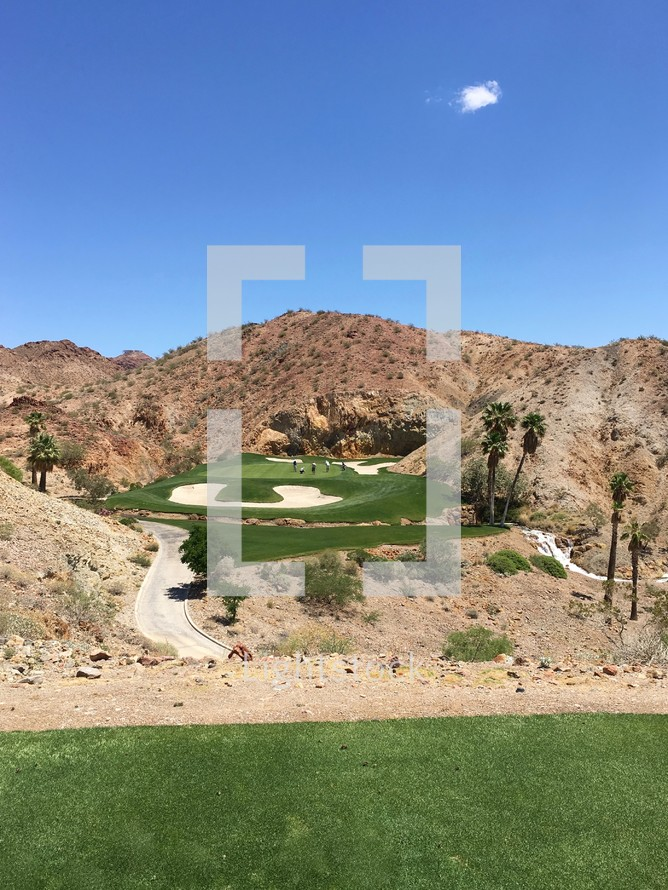 golfers on a golf course surrounded by desert mountains in Nevada