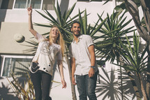a man and a woman standing outdoors in front of tropical plants