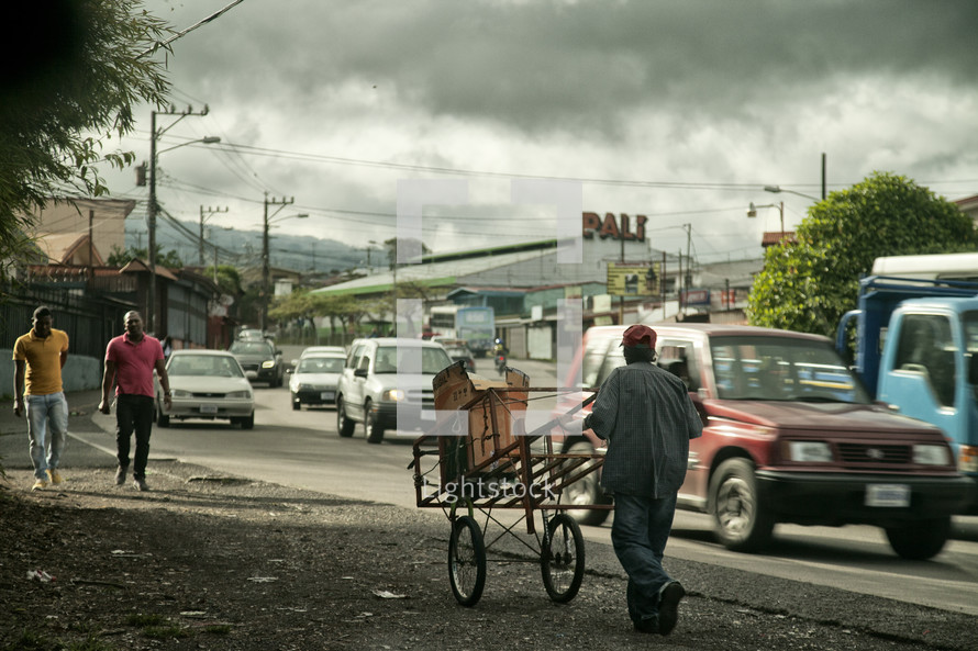 man pushing a cart along the side of a road