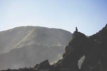 man sitting on a rock peak praising the Lord