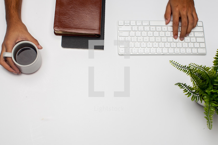 a man at a desk with a keyboard typing and a Bible