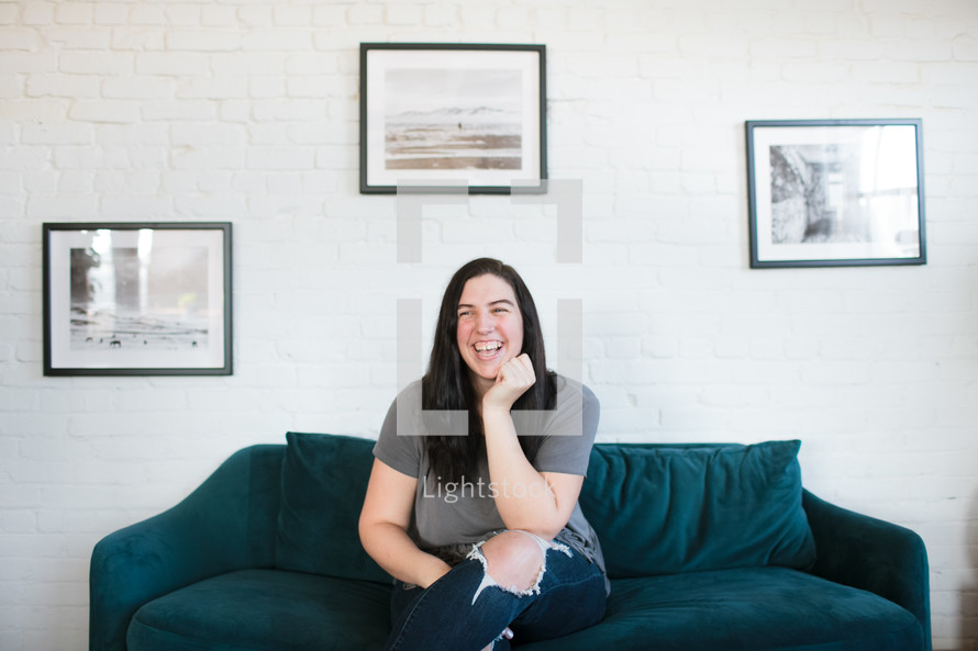 a smiling girl sitting on a couch