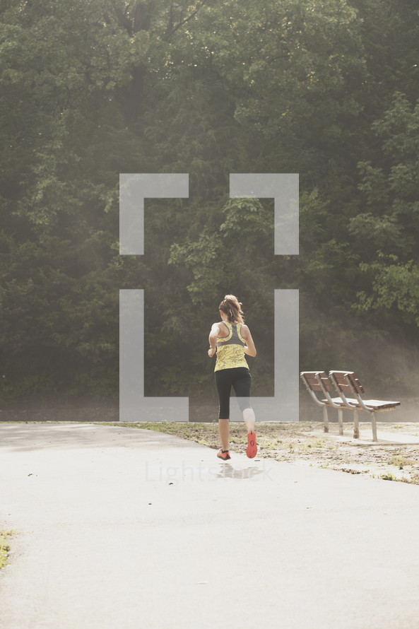 Woman jogging through a park.