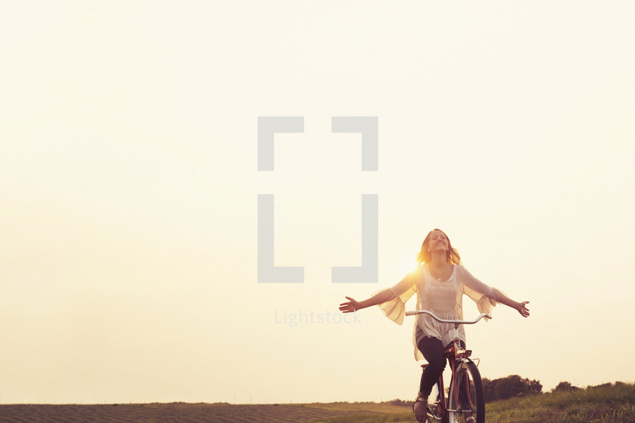 teenage girl riding a bicycle at sunset.