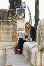 A woman sitting on a stone wall reading a Bible in Jerusalem