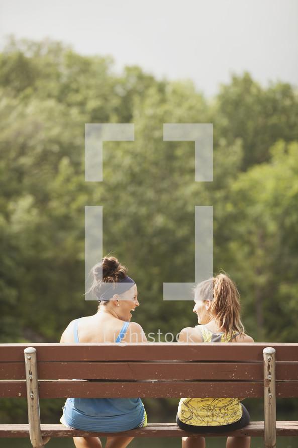 women sitting on a park bench talking